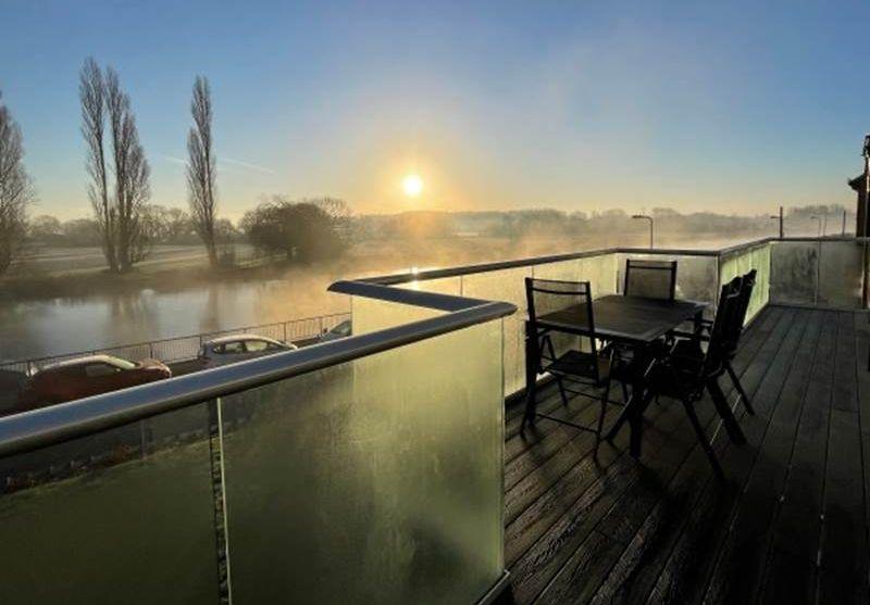 Early morning mist envelopes angled glass balcony